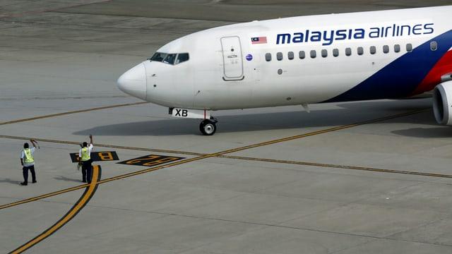 Zwei Flughafenmitarbeiter leiten ein Flugzeug der Malaysia Airlines an