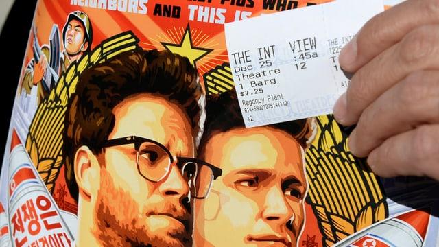 Filmplakat von «The Interview» und jemand, der ein Kinoticket davor hält.