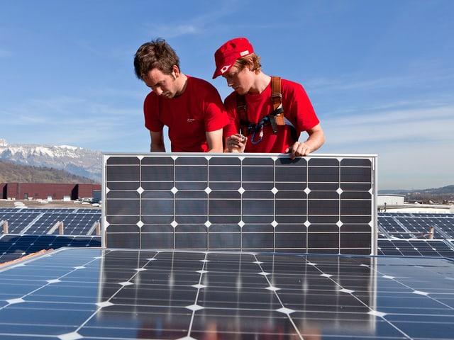 Zwei Männer montieren Solar-Panels