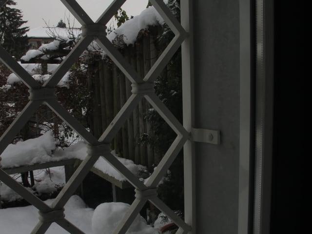Blick aus einem vergitterten Fenster in den verschneiten Garten.