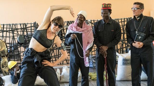 Drei Männer und eine Frau tanzen auf einer Bühne.