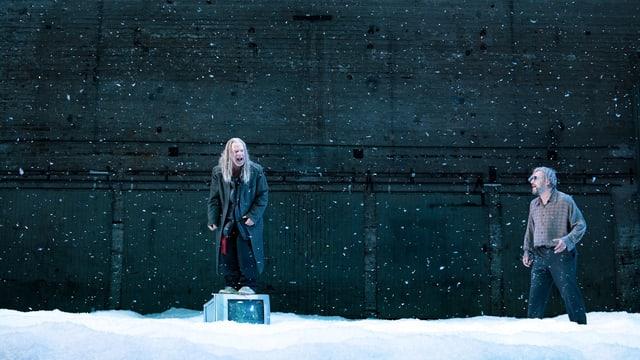 Zwei Männer auf einer Bühne. Es schneit, auf dem Boden liegt Schnee.