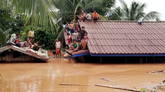 Menschen stehen und sitzen auf Dächern, ihre Häuser stehen unter Wasser