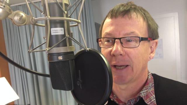 Mann mit Brille spricht in Mikrofon