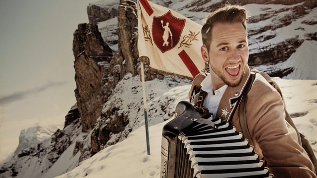 Trauffer vor Fahne an Berggipfel.