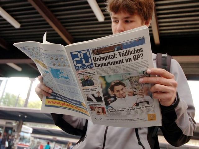 Junger Mann liest die Gratiszeitung «20 Minuten».