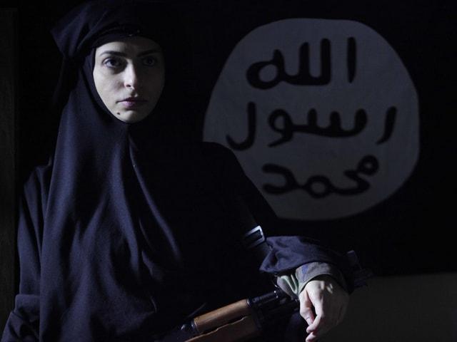 Eine Frau im Dschador mit einem Gewehr.
