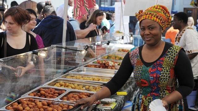 Ein Marktstand mit Essen und einer bunt gekleideten Verkäuferin