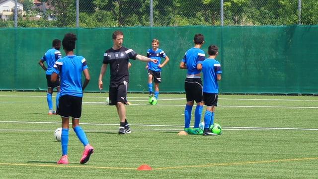 Ein Trainer in schwarzen kurzen Hosen gibt Anweisungen an Fussballjunioren, die auf dem Platz herumstehen mit einem Ball am Fuss.