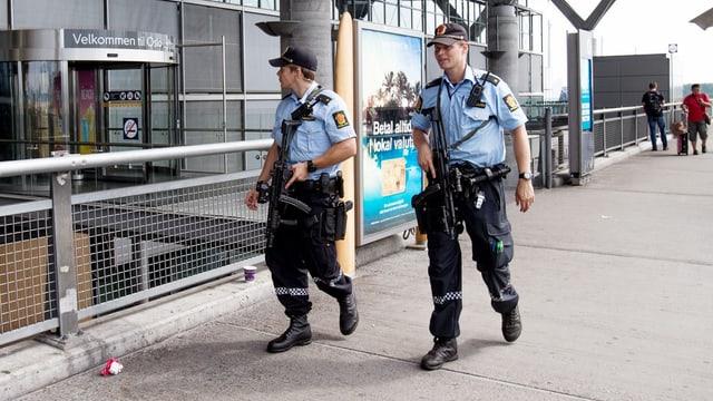 Zwei Polizisten gehen nebeneinander ausserhalb des Terminals des Osloer Flughafens.