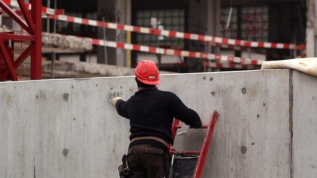 Bauarbeiter auf einer Leiter.