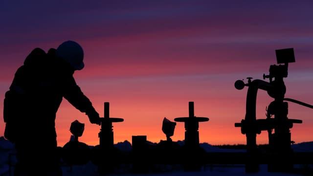 Symbolbild: Ein Mann dreht an einem Ölhahn, dahinter Morgenrot-
