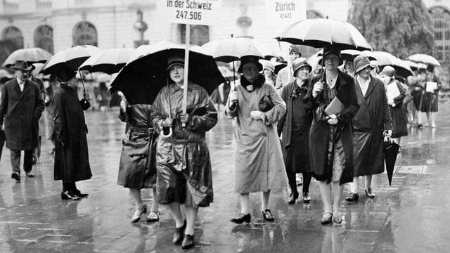 Eine Gruppe von Frauen protestiert im Regen für das Frauenstimmrecht.