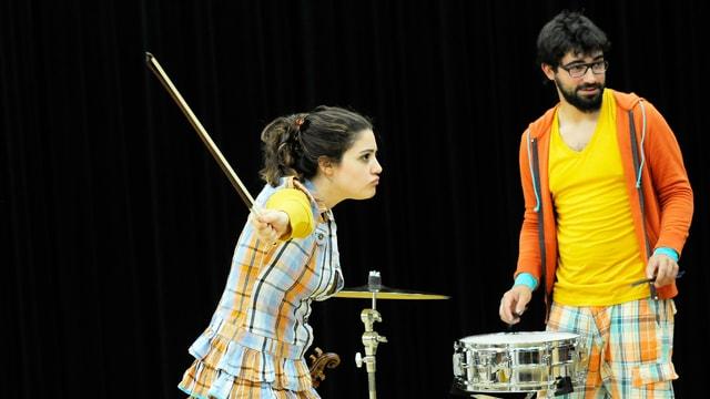 Eine junge Frau mit einem Geigenbogen geht über die Bühne. Im Hintergrund ein junger Mann mit Schlagzeug.