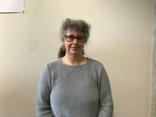Im Bild ist Claudia Spiess von der Uni Zürich. Sie leitet das Forschungsprojekt Disabeld in Politics. Sie ist eine ältere Frau mit grauen langen Haaren und Brille im grauen Pullover.