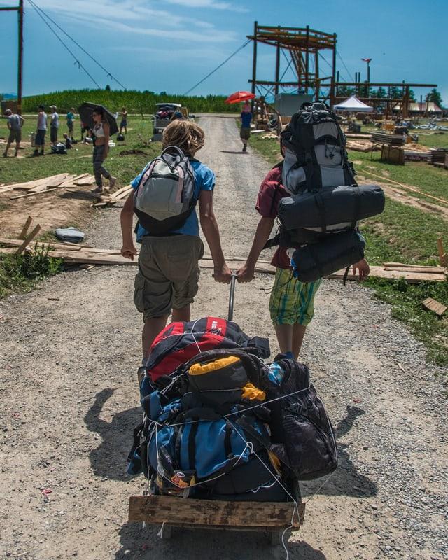 2 Jugendliche verlassen mit Rucksäcken den Lagerplatz