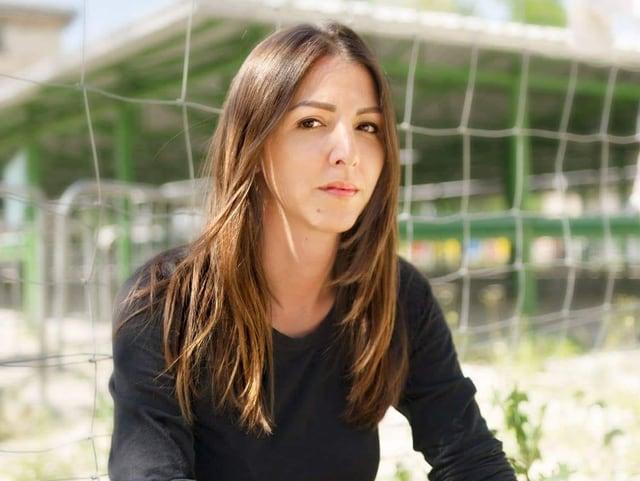 Ein Porträtfoto von Vanja Crnojevic, einer jungen Frau, mit braunen Haaren und schwarzem Pullover. Sie sitzt vor einem Zaun und blickt enschlossen in die Kamera.