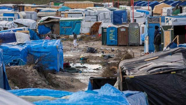 Zelte und Sanitärhäuschen auf schlammigen Boden