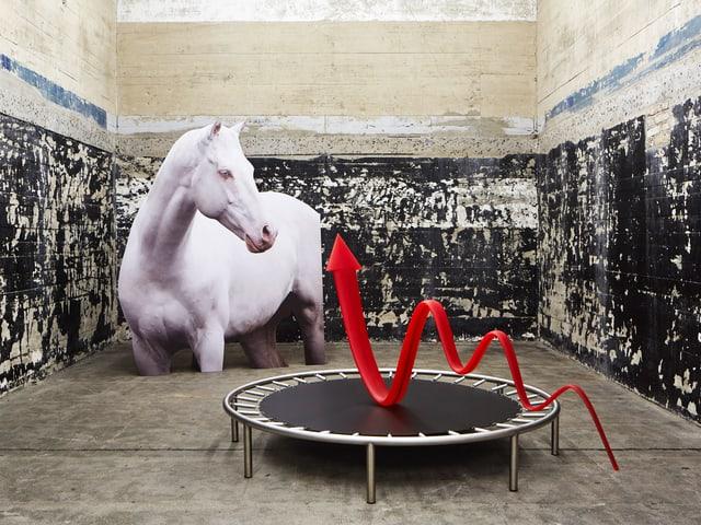 Raum mit schwarz bemalten Betonwänden, darin Skulptur eines Pferdes