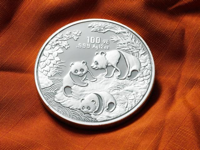 Eine silberne Münze mit drei Pandabären als Motiv und chinesischen Schriftzeichen.
