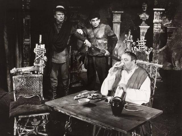 Ein Mann sitzt an Tisch und frühstückt, zwei Männer sehen ihm zu.