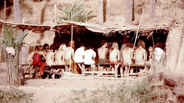Eine Gruppe junger, nackter Leute sitzt in einer Strohhütte einer Strandbar.