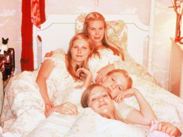 Vier Schauspielerinnen liegen auf einem Bett.
