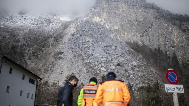Einsatzkräfte begutachten das Felssturzgebiet bei Felsberg.