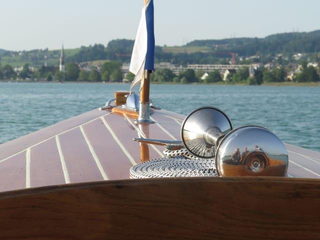 Blick über Bug eines Motorboots auf Dorf am Ufer