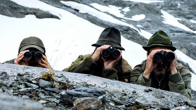 Drei Männer vin Jagdkleidung verstecken sich hinter einem Stein und schauen durch Ferngläser.