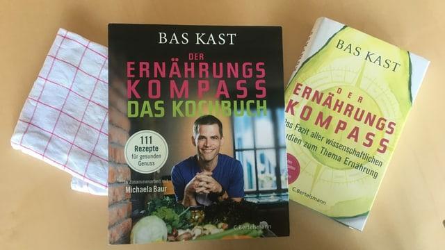 2 Kochbücher auf einer Holzunterlage.