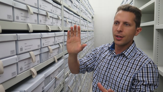 Adrian Oettli vom Staatsarchiv Thurgau steht vor vielen Schachteln mit Archiv-Dokumenten