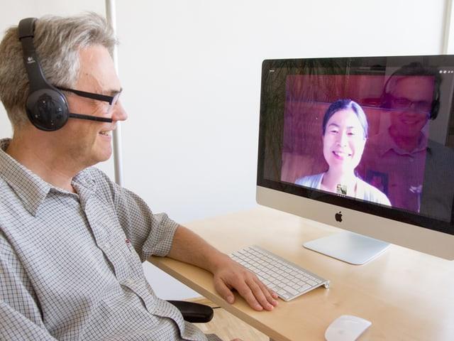 Ein Mann mit Head-Set sitzt vor einem Bildschirm, darauf eine asiatische Frau, die beiden unterhalten sich.