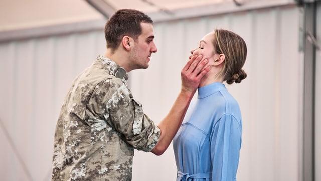 Ein Mann hält gewaltvoll den Kopf einer Frau.
