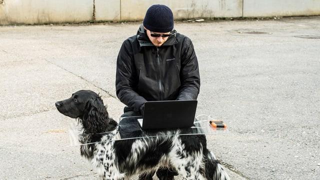 Lukas Wassmann schaut auf einen Laptop. Der Laptop steht auf einem transparenten Tisch, den ein Hund trägt.