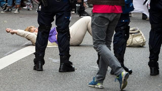Frau liegt am Boden, davor die Beine von Polizisten und anderen Personen