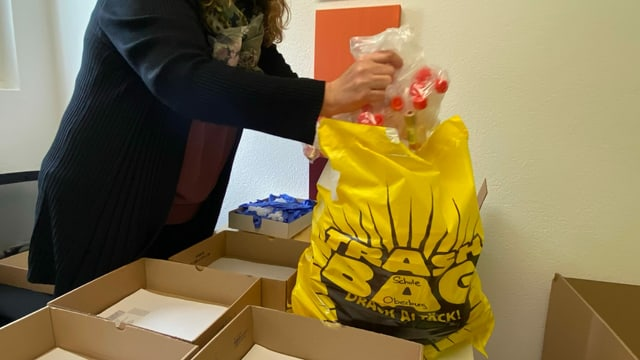 Die Sekretärin packt die Säckli in einen gelben Sack.