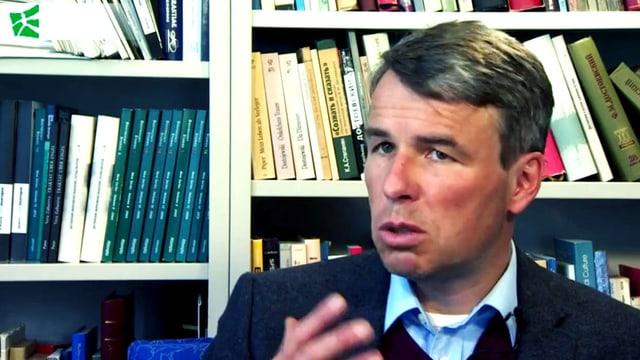 Ulrich Schmid vor einem Büchergestell, gestikulierend.