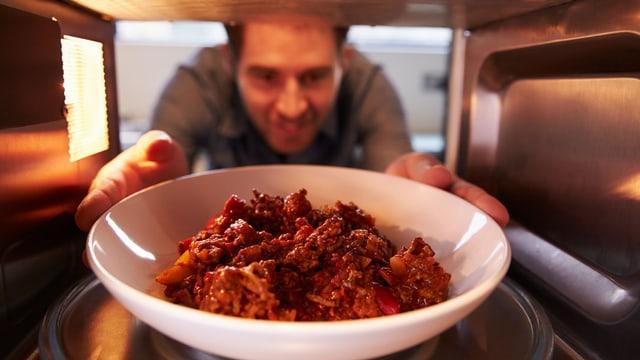 Ein Mann schiebt einen Teller mit Fleisch in einen Mikrowellenherd.