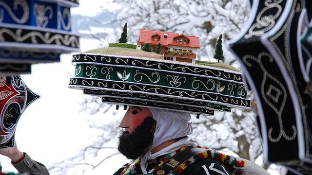 Eine Person mit farbenfroher Haube und Maske.