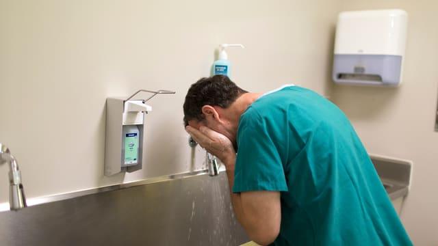 Ein Arzt wäscht sich vor einer Operation