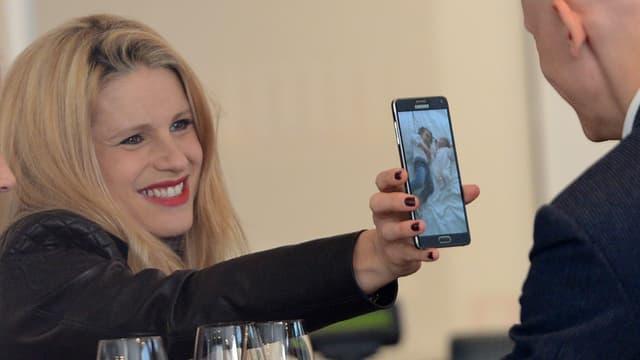 Michelle Hunziker hält einem Mann ein Telefon hin. Auf dem Telefon ist ein Bild von zwei Babys zu sehen.