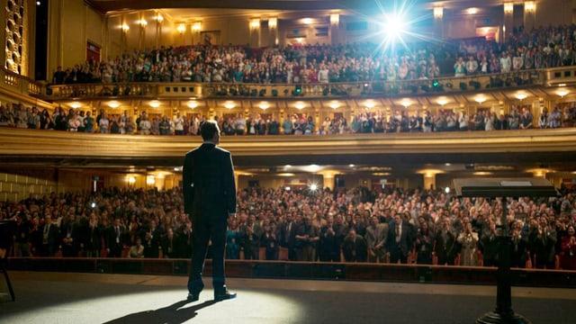 Blick von hinten auf eine Bühne: Ein Mann steht alleine auf der Bühne vor dem Publikum.