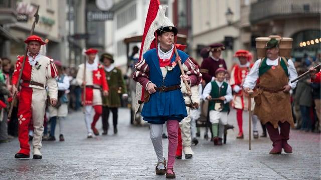Mehrere Männer laufen in Kostümen und rot-weiss-gekleidet durch St. Gallen.