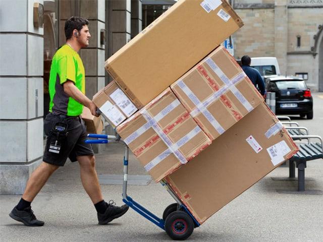 Ein Kurier transportier einen Stapel Pakete