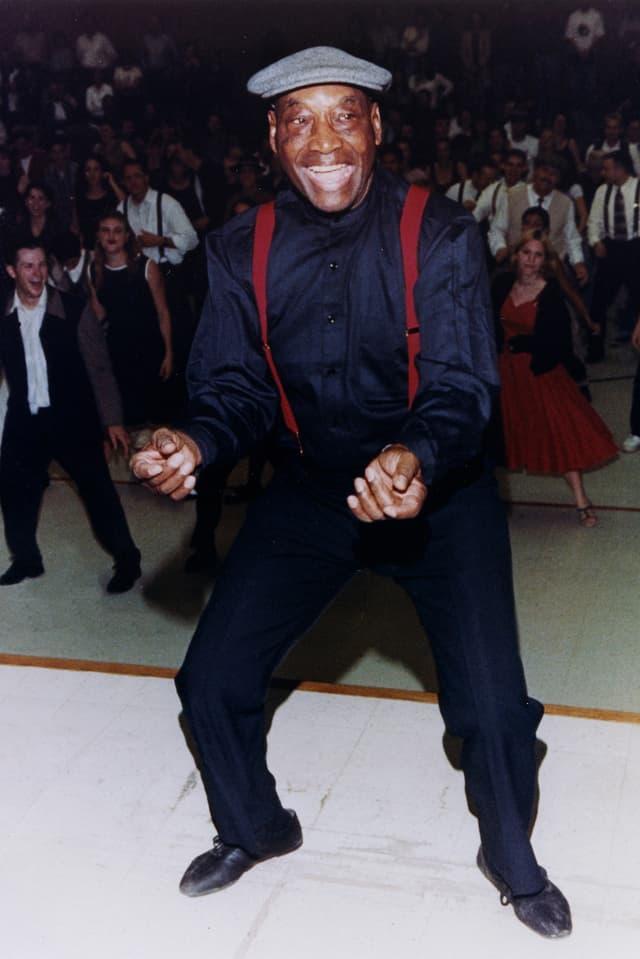 Frankie Manning leitet einen Shim Sham, ein Tanz aus den 1920er-Jahren. Hinten tanzen Menschen.
