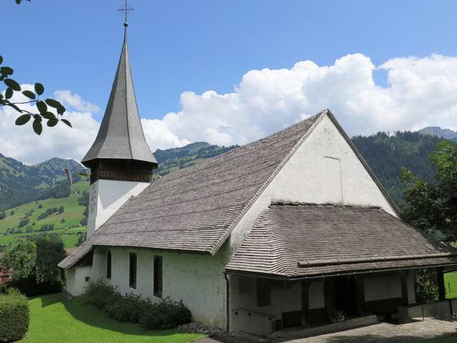 Eine Kirche, am Horizont Wolken und Berge.