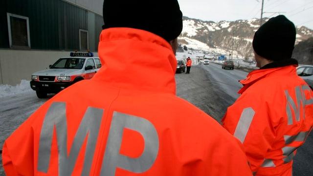 Polizisten in oranger Uniform von hinten