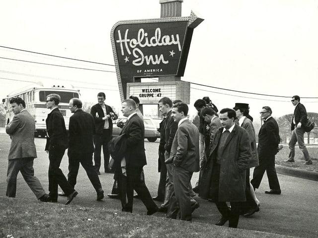 Eine Gruppe mit Männern in Anzügen vor einem Schild mit der Aufschrift «Holiday Inn».