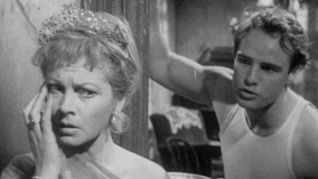 Blanche, mit verängstigtem Blick, fasst sich mit der rechten Hand ins Gesicht. Stanley steht hinter ihr und redet auf sie ein.